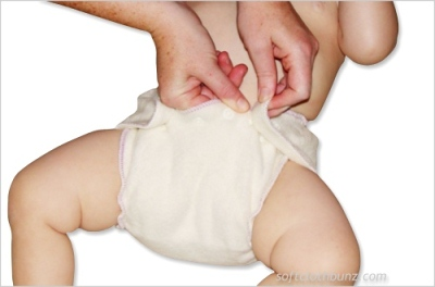 Snap the wings on the back of the diaper to the front of the diaper, securing the fitted on baby.